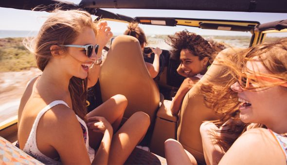 Afro girl laughing with friends on a road trip vacation